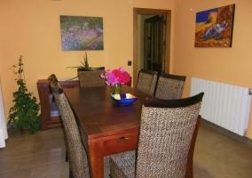Mesa del comedor con seis sillas y cuadros en las paredes de la sala