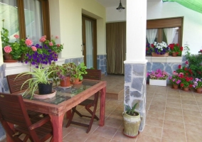 Porche de la entrada con mesa y sillas y plantas