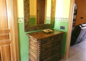 Recibidor con paredes verdes y espejo sobre mueble