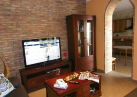 Salón con televisor sobre mueble y mesa baja delante