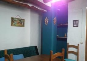 Estufa de leña en el salón comedor delante de la mesa de madera