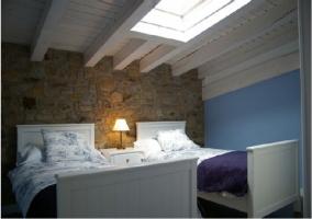 Habitación doble con camas individuales y pared de piedra