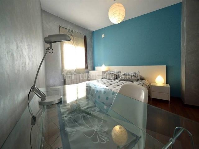 Dormitorio con pared azul y cama doble