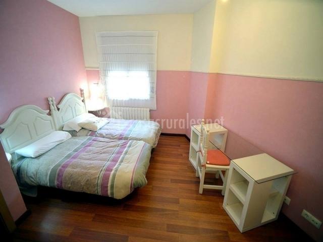 Dormitorio con paredes rosas y dos camas