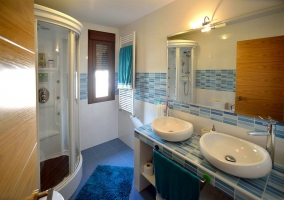 Aseo con dos lavabos y azulejos azules