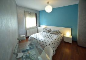 Dormitorio con cama doble y cabecero blanco