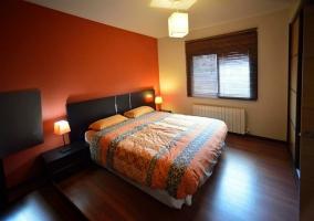 Dormitorio con cama doble y pared naranja
