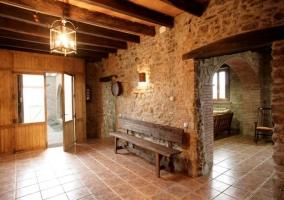 Entrada a la casa con pared de piedra y bancos