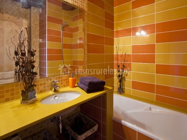 Baño con bañera naranja y amarillo