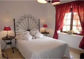 Dormitorio con cama doble roja de la casa rural