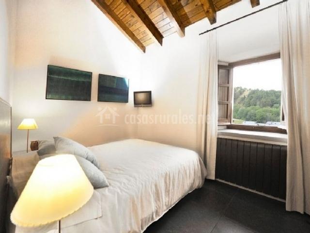 Cama grande y ventana con cortinas blancas