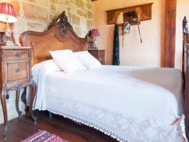 Dormitorio de matrimonio con colcha en color blanco y elegante cabecero