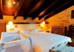 Dormitorio de matrimonio con techos de madera y cuna