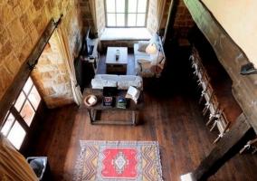 Sala de estar con suelos de madera y rincones con el televisor