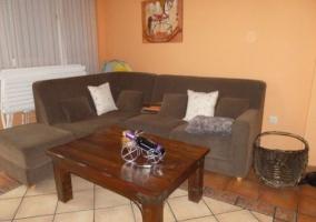 Sala de estar con muebles de madera y televisor junto a la cocina