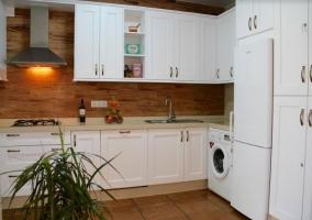 Cocina con frente en madera y muebles blancos