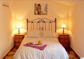 Dormitorio de matrimonio con colcha blanca y desayuno