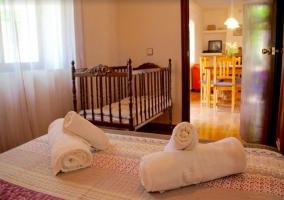 Dormitorio de matrimonio con cuna y su aseo