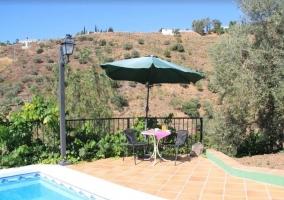 Vistas de la piscina con zona de mesas y sillas