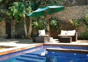 Piscina en el jardín con sillones, sombrilla y tumbonas