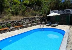 Vistas de la piscina climatizada con sombrilla y hamacas