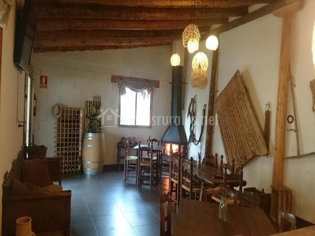 Bodega de la casa rural con chimenea de leña y varias mesas para organizar eventos o comer