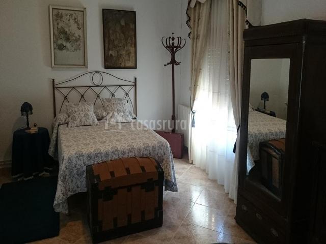 Habitación con cama de matrimonio y baúl de madera a los pies