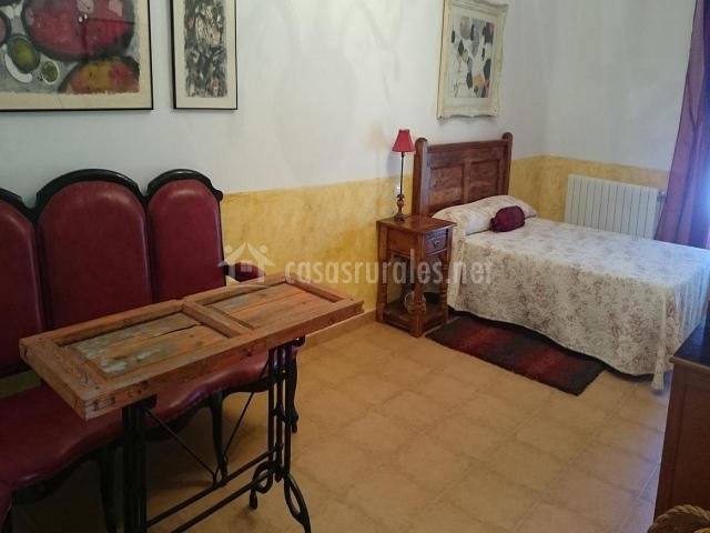 Habitación con cama de matrimonio y original mesa realizada con una antigua puerta de madera