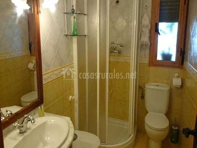Uno de los baños de la casa rural con azulejos amarillos y plato de ducha