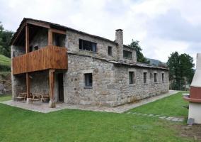 Fachada  de piedra con terraza de madera