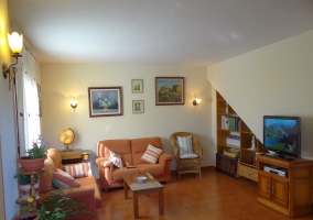 Sala de estar con dos sillones naranjas frente al televisor