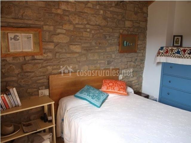 Dormitorio de matrimonio con paredes de piedra y muebles coloridos