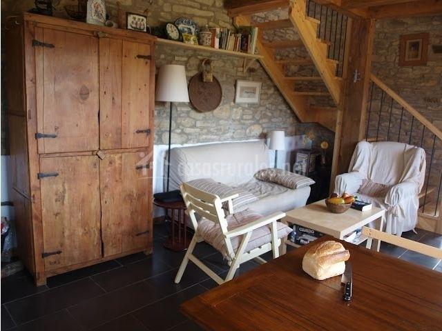 Sala de estar con mueble de madera y paredes de piedra