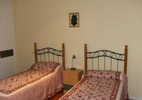 Dormitorio con 2 camas con colchas de hojas rojas