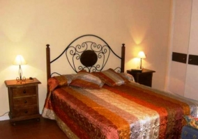 Dormitorio con cama de matrimonio y cabecero de hierro forjado