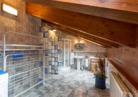 Amplio baño con baldosas y techo de madera con vigas