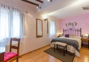 Amplia habitación doble con cama de matrimonio y cabecero de diseño