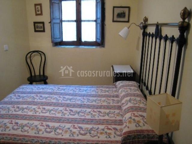Dormitorio de matrimonio con ventana y mesillas