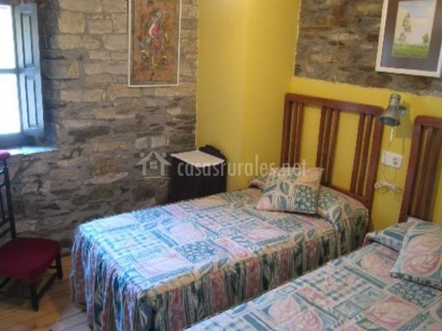 Dormitorio doble con pared en amarillo y piedra