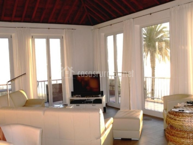Sala de estar con cristaleras y sillones en blanco