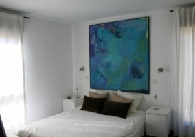 Dormitorio de matrimonio con cuadro y colchas en blanco