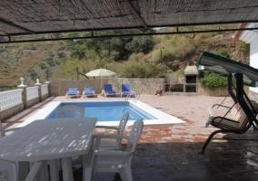 Zona techada y piscina con hamacas