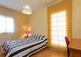 Dormitorio de matrimonio con colcha de rayas