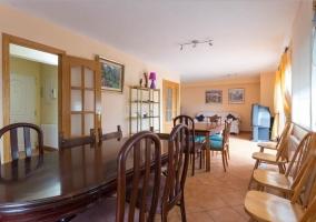 Sala de estar y comedor con mesa de madera oscura