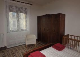 Habitación de matrimonio blanca con cuna y armario