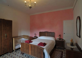 Habitación de matrimonio blanca con pared rosa