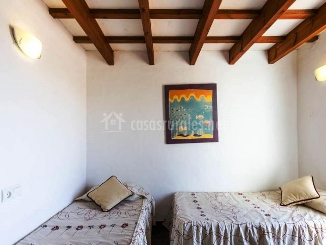 Dormitorio doble en blnaco con techo de vigas de madera