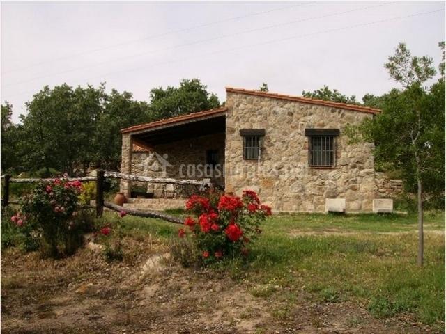 Fachada exterior de piedra con flores rojas y rosas