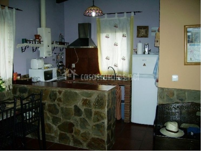 Cocina con electrodomésticos. Barra americana de piedra