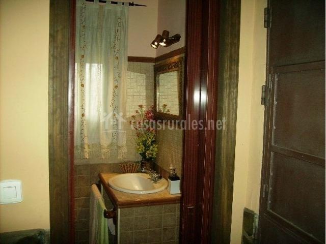 Cuarto de baño con flores y lavabo sobre un mueble